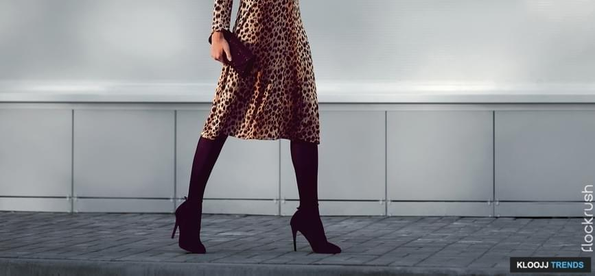 Street fashion concept - stylish elegant woman in leopard dress on heels with clutch handbag walking in the city