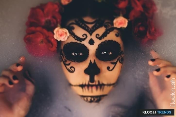 Beautiful woman with halloween sugar skull make-up and flowers in her hair.